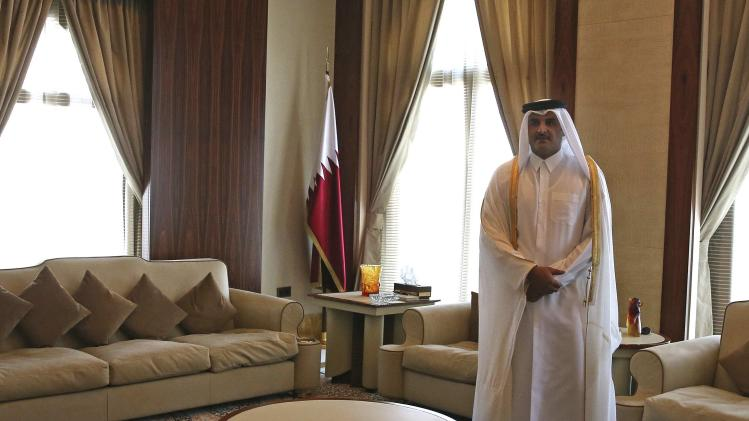 Qatar's Emir Sheikh Tamim waits for the arrival of U.S. Secretary of Defense Chuck Hagel in Doha