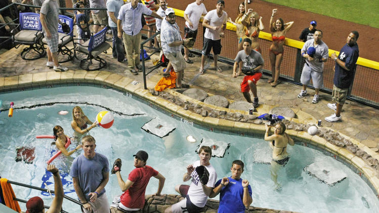 FILE - This July 11, 2011 file photo shows a home-run ball falls into the pool during baseball' All-Star Home Run Derby at Chase Field in Phoenix. All the baseball teams are based in major U.S. cities and many of the stadiums are situated in bustling downtown areas with engrossing things to do and savory places to eat when you aren't attending a game. These attractions should help the cause of baseball fans trying to recruit a spouse or other traveling teammates who may not appreciate the sublime pleasures of the game. (AP Photo/The Arizona Republic, Rob Schumacher) MARICOPA COUNTY OUT  NO SALES