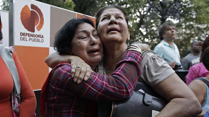Supporters of Venezuela's President Hugo Chavez weep as she learn that Chavez has died through an announcement by the vice president in Caracas, Venezuela, Tuesday, March 5, 2013. Venezuela's Vice President Nicolas Maduro announced that Chavez died on Tuesday at age 58 after a nearly two-year bout with cancer. During more than 14 years in office, Chavez routinely challenged the status quo at home and internationally. He polarized Venezuelans with his confrontational and domineering style, yet was also a masterful communicator and strategist who tapped into Venezuelan nationalism to win broad support, particularly among the poor. (AP Photo/Ariana Cubillos)