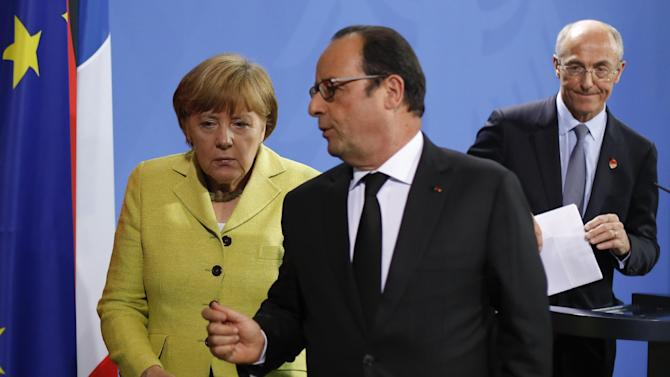 German Chancellor Angela Merkel, left, listens to the President of France Francois Hollande, center, after a statement for the media prior to a meeting at the chancellery in Berlin, Germany, Monday, June 1, 2015. Right are the President of the European Round Table of Industrialists Benoit Potier. (AP Photo/Markus Schreiber)