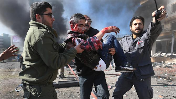Lebanese men carry an wounded man at the site of an explosion, near the Kuwaiti Embassy and Iran's cultural center, in the suburb of Beir Hassan, Beirut, Lebanon, Wednesday, Feb. 19, 2014. A blast in a Shiite district in southern Beirut killed at least two people on Wednesday, security officials said — the latest apparent attack linked to the civil war in neighboring Syria. (AP Photo/Hussein Malla)