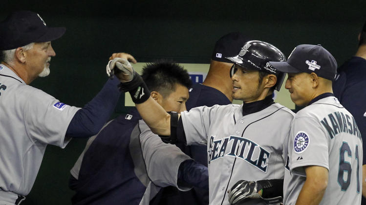 Seattle Mariners' Ichiro Suzuki, second left, celebrates with pitching coach Carl Willis at the dugout after hitting an RBI single in the 11th inning in Tokyo, Wednesday, March 28, 2012. At right is teammate Munenori Kawasaki. (AP Photo/Koji Sasahara)