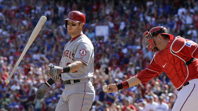 Los Angeles Angels' Josh Hamilton (32) flings the bat in the air after striking out swinging as Texas Rangers catcher A.J. Pierzynski (12) applies the tag in the fourth inning of a baseball game Saturday, April 6, 2013, in Arlington, Texas. (AP Photo/Tony Gutierrez)