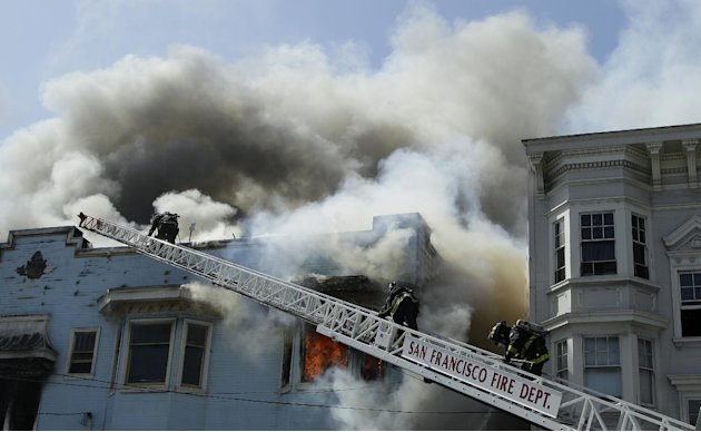 San Francisco firefighters battle a four-alarm fire at a residential and commercial building on the corner of Valencia Street and Duboce Avenue in San Francisco, Sunday, May 6, 2012. (AP Photo/Jeff Ch
