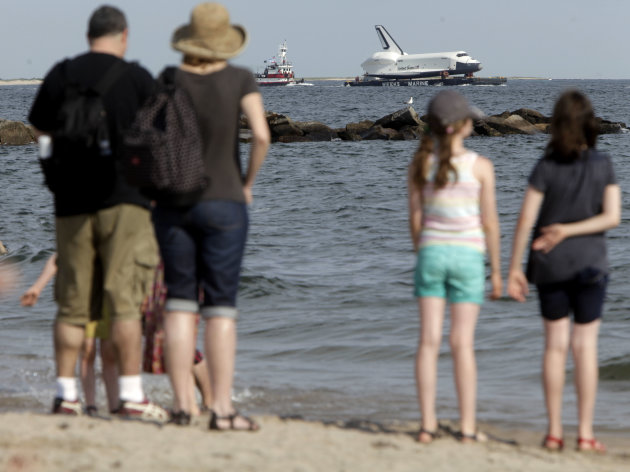 Spectators watch the space shuttle Enterprise as it is towed past a beach at Coney Island in New York, Sunday, June 3, 2012.  The prototype space shuttle that arrived in New York City by air earlier t