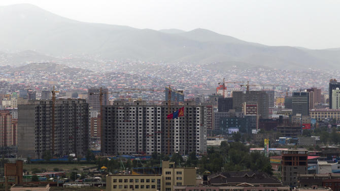In this July 4, 2012 photo, a Mongolian national flag flutters in the wind near an apartment building under construction in downtown Ulan Bator, Mongolia. Landlocked with 2.8 million people spread over an area twice the size of Texas, Mongolia is dwarfed by China, with its 1.3 billion people and the world's second largest economy. Fully 90 percent of Mongolia's exports - coal, copper, cashmere and livestock - go to China, which in turn sends machinery, appliances and other consumer goods that account for a third of Mongolian imports. (AP Photo/Andy Wong)