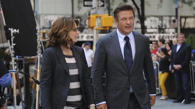 "This undated photo released by NBC shows Tina Fey, left, and Alec Baldwin on the set of their comedy series ""30 Rock,"" in New York. As NBC's new owner Comcast Corp., makes changes to reboot the fourth-place network, Baldwin has tweeted he'll cut his salary to keep ""30 Rock"" on the air.  (AP Photo/NBC, Ali Goldstein)"
