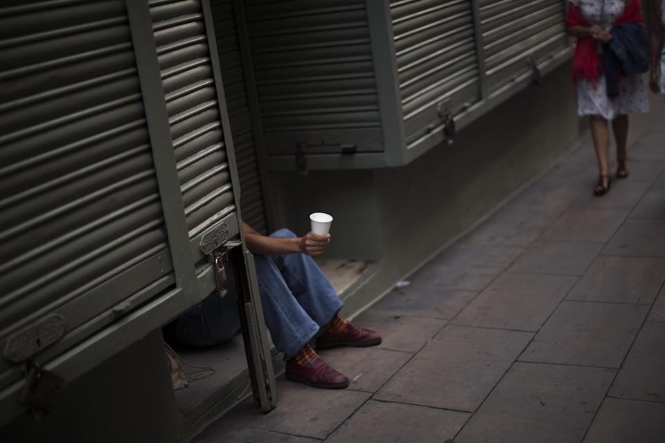 A man holds a cup as he begs in a street in Barcelona, Spain, Saturday June 9 2012. Spain will ask for a bank bailout from the eurozone, becoming the fourth and largest country to seek help since the single currency bloc's debt crisis erupted. (AP Photo/Emilio Morenatti)