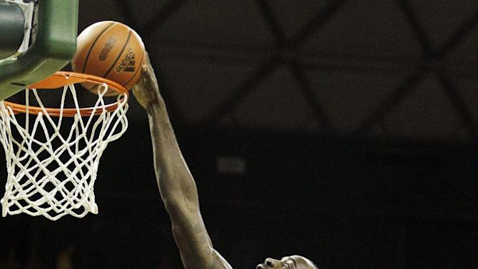 Baylor forward Quincy Acy (4) dunks over Bethune-Cookman guard Paul Scotland (3) as Ricky Johnson, rear, looks on in the first half of an NCAA college basketball game, Wednesday, Dec. 14, 2011, in Waco, Texas. (AP Photo/Tony Gutierrez)