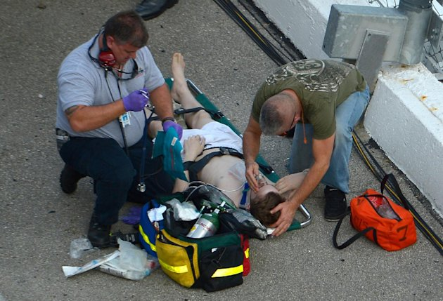 Emergency personnel attend to an  injured spectatos in front of the grandstands after Kyle Larson's car hit the safety wall and fence along the front stretch on the final lap of the NASCAR Nationwide 