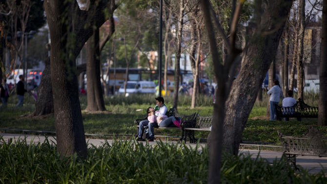 A couple occupy a bench in Alameda Central in Mexico City, Wednesday, Dec. 26, 2012.  Instead of a motley patchwork of folding tables and tarps, the newly opened park is a sea of greenery and calm in the midst of racing traffic. Mexico City's government is trying to transform one of the world's largest cities by beautifying public spaces, parks and monuments buried beneath a sea of honking cars, street hawkers, billboards and grime following decades of dizzying urban growth. (AP Photo/Alexandre Meneghini)