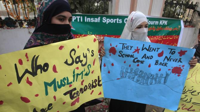 Women hold placards to condemn the Taliban attack on the Army Public School in Peshawar
