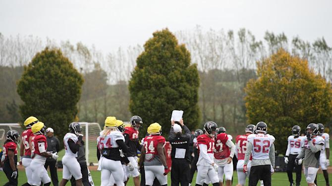Atlanta Falcons check a play during a training session at the Arsenal FC training ground in London Colney, England, Wednesday Oct. 22, 2014. The Falcons will play the Detroit Lions in an NFL football game at London's Wembley Stadium on Sunday, Oct. 26