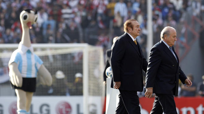 Followed by Suri, the mascot of the Copa America 2011, left, FIFA's President Sepp Blatter, right, and CONMEBOL's President Nicolas Leoz walk the field before the Copa America final soccer match between Uruguay and Paraguay in Buenos Aires, Argentina, Sunday, July 24, 2011. (AP Photo/Natacha Pisarenko)