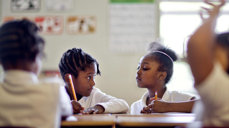 In this Thursday, April 18, photo, Burgess-Peterson Elementary School first graders Jacqueline Wright, left, and Kennedy Thomas, work through a lesson as part of Atlanta Public School's after-school remediation program in Atlanta. Anxiety is high among students and teachers with state standardized tests set to begin Tuesday. A lot of focus and criticism has been aimed at the tests, known as CRCT in Georgia, since one of the nation's largest cheating scandals erupted within the Atlanta Public Schools system a few years back that included allegations that teachers and principals changed scores to inflate performance. While criminal charges are pending against 35 former Atlanta educators, the district has been working on a system-wide remediation program aimed at helping those directly affected by the cheating scandal and others who have simply fallen behind. (AP Photo/David Goldman)