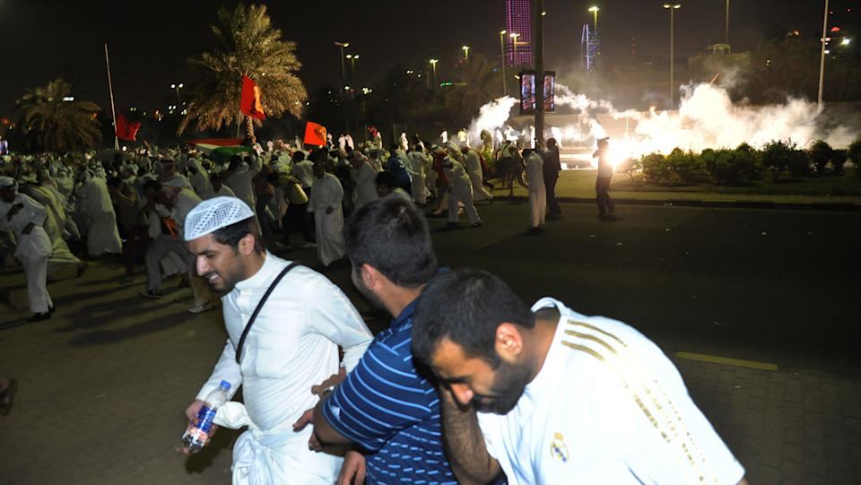 Kuwaiti men run away from police tear gas during a demonstration in Kuwait City on Sunday, October 21, 2012. Several thousand protestors from opposition groups, Bedouin tribes and former MPs gathered in different points of Kuwait City to demonstrate against the Government's amendment of the country electoral law.(AP Photo/Gustavo Ferrari)
