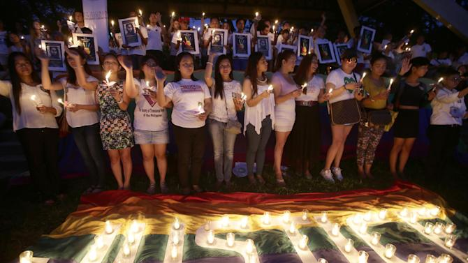 """Protesters, mostly from LGBT (Lesbians Gays Bisexual and Transgenders) community light candles at the University of the Philippines campus at suburban Quezon city, northeast of Manila, to demand justice in the killing of Filipino transgender Jeffrey """"Jennifer"""" Laude, Friday, Oct. 24, 2014, the day of his funeral in Olongapo city in western Philippines. U.S. Marine Pfc. Joseph Scott Pemberton is being tagged as a suspect and is now detained in a U.S. facility inside the sprawling general headquarters of the Philippine armed forces. (AP Photo/Bullit Marquez)"""