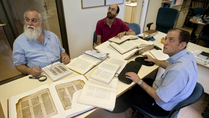 In this photo taken Wednesday, Aug. 10, 2011, Dr. Michael Segal, editor for the Hebrew University Bible Project, right, Dr. Rafael Zer, editorial coordinator, left, Assaf Rosen-Zvi, coordinator for rabbinic literature, confer in their office at the Hebrew University in Jerusalem. For many Jews and Christians, religious beliefs dictate that the words of the Bible are divine, unaltered and unalterable. But the ongoing work of the academic detectives of the Bible Project, as their undertaking is known, shows that this foundation text of Western civilization has always been more fluid than these beliefs would suggest, and that its transmission through the ages was messier and more human than most of us imagine. (AP Photo/Sebastian Scheiner)