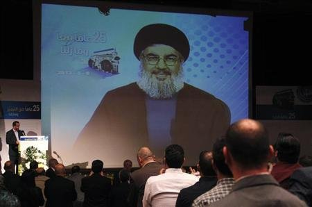 People applaud as Lebanon's Hezbollah leader Nasrallah appears on a screen during a live broadcast at an event marking the 25th anniversary of the establishment of Al-Nour radio station in Beirut