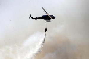 A helicopter dumps water on a forest fire in Valparaiso,…