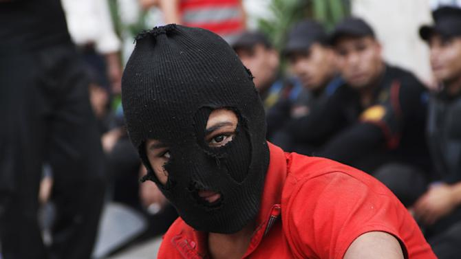 An Egyptian protester attends a demonstration outside the Defense Ministry in Cairo, Egypt, Wednesday, May 2, 2012. Suspected supporters of Egypt's military rulers attacked predominantly Islamist anti-government protesters outside the Defense Ministry in Cairo Wednesday, setting off clashes that left more than ten people dead as political tensions rise three weeks before crucial presidential elections. Egyptian police officers are seen, background. (AP Photo/Ahmed Gomaa)