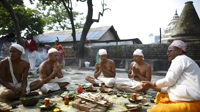 Family members perform religious ritual for the victims of the April 25 earthquake in Kathmandu