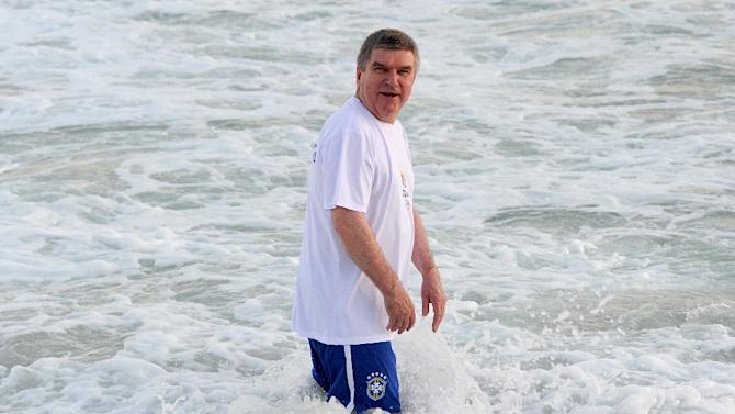 International Olympic Committee president Thomas Bach enters the waters at an event at Barra da Tijuca Beach in Rio de Janeiro, Brazil, on August 4, 2015, one year before the start of the Rio 2016 Olympic Games