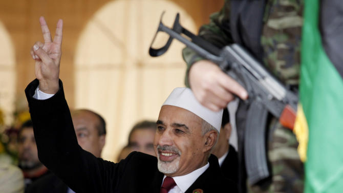 FILE - In this Sunday, Feb. 17, 2013 file photo, Libyan interim president, Mohammed el-Megarif flashes the victory sign to the crowd during the celebration of the second anniversary of the Libyan revolution in Benghazi, Libya. The head of Libya's elected parliament has announced his resignation on Tuesday, May 28, 2013, just weeks after the body he led passed a law that bans officials who served under ousted dictator Moammar Gadhafi from senior government posts. Al-Megarif, who was Libya's ambassador to India in 1980 before he joined the opposition in exile, teared up as he wished his country well and announced he is stepping down. (AP Photo/Mohammad Hannon, File)