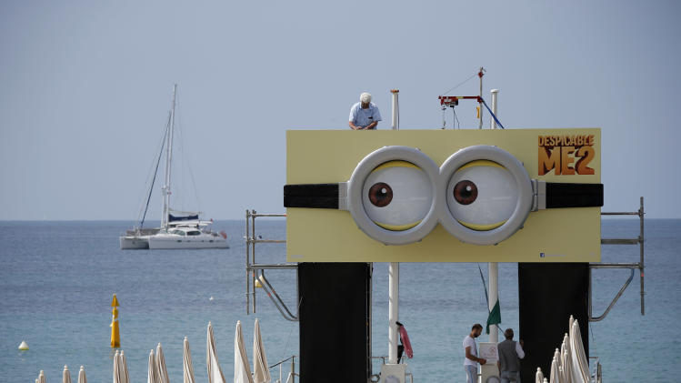 Workers set up a hoarding advertising a film ahead of the 66th international film festival, in Cannes, southern France, Tuesday, May 14, 2013. (AP Photo/Lionel Cironneau)