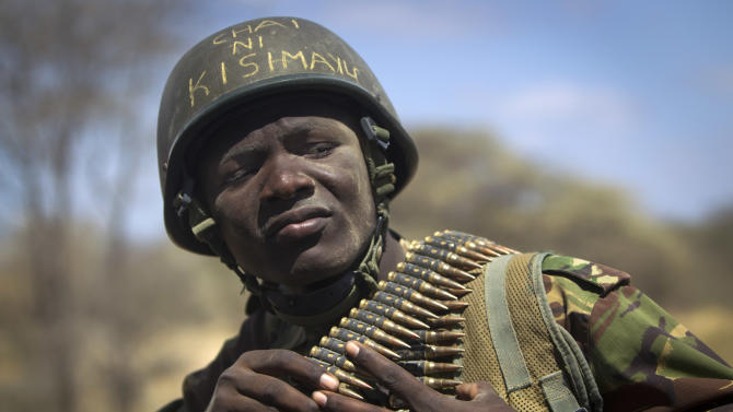 """FILE - In this Tuesday, Feb. 21, 2012 file photo, Kenyan army soldier Nicholas Munyanya, wearing a helmet on which is written in Kiswahili """"Tea in Kismayo"""", referring to a key strategic Somali town then under the control of al-Shabab, checks his ammunition belt near the town of Dhobley, in Somalia. Kenya's military said Friday, Sept. 28, 2012 that its troops attacked Kismayo, the last remaining port city held by al-Qaida-linked al-Shabab insurgents in Somalia, during an overnight attack involving a beach landing. (AP Photo/Ben Curtis, File)"""