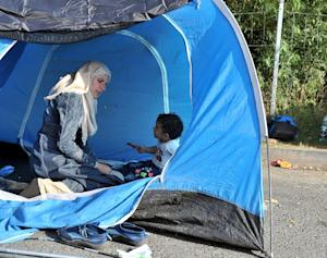 A woman and a child shelter in a tent on the highway …