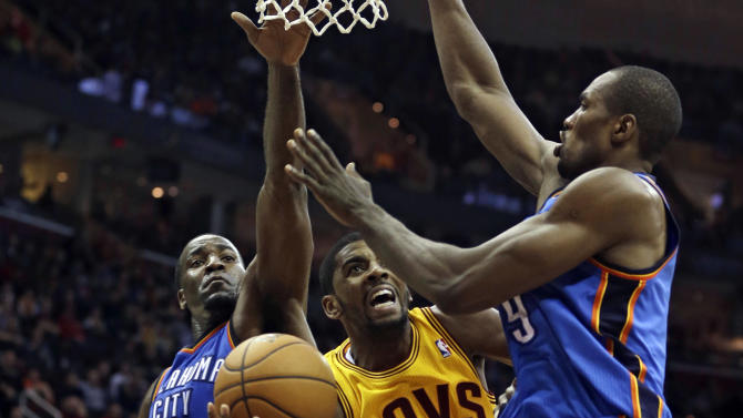 Cleveland Cavaliers' Kyrie Irving (2) shoots to the basket against Oklahoma City Thunder's Kendrick Perkins (5) and Serge Ibaka (9), from the Republic of Congo, during the fourth quarter of an NBA basketball game on Saturday, Feb. 2, 2013, in Cleveland. The Cavaliers won 115-110. (AP Photo/Tony Dejak)