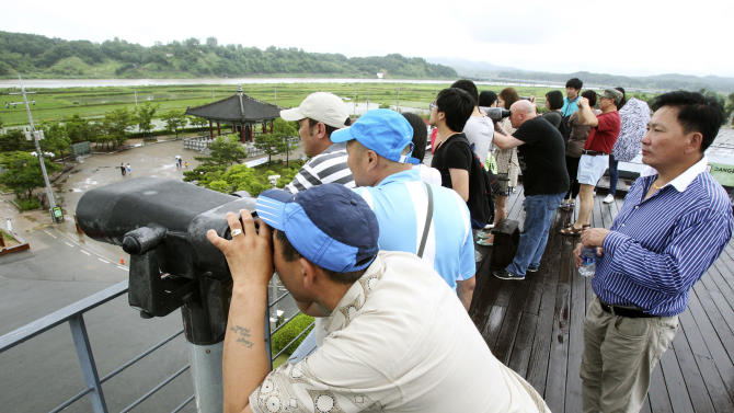Visitors look toward North Korea at the Imjingak Pavilion near the border village of Panmunjom in Paju, South Korea, Wednesday, June 12, 2013. The Koreas' first high-level talks in years have been scrapped because of a stalemate over who will lead each delegation, South Korea said Tuesday, a day before they were to begin. The cancellation is a blow to tentative hopes that the rivals were about to improve ties following years of rising hostility. (AP Photo/Ahn Young-joon)
