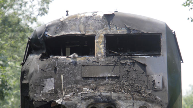 The charred engine of the Amtrak train that collided into a tractor-trailer is seen Monday, July 11, 2011 in North Berwick, Maine. Both were set on fire an official said and the truck driver was killed. Some of the train's 109 passengers were injured, but it's not clear how many or how seriously they were hurt, said an official.  The crash happened at about 11 a.m. in North Berwick, about 40 miles south of Portland. (AP Photo/Pat Wellenbach)