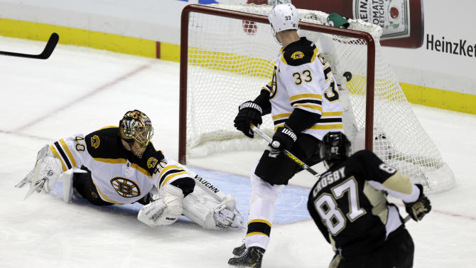 Pittsburgh Penguins center Sidney Crosby (87) gets the puck behind Boston Bruins goalie Tuukka Rask (40) and Bruins defenseman Zdeno Chara (33) for a goal during the first period of an NHL hockey game in Pittsburgh, Sunday, March 17, 2013. (AP Photo/Gene J. Puskar)