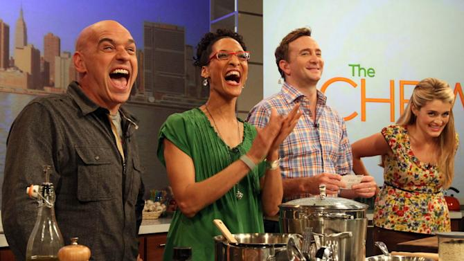 "This Friday, Aug. 26, 2011 photo shows co-hosts of ABC's ""The Chew"", from left to right, Iron Chef Michael Symon, Carla Hall, Clinton Kelly and Daphne Oz as they react to audience applause during a rehearsal of the show in New York. Can some of food and style TV's biggest stars help ABC soap fans get over cancellation of their favorite stories? The network's counting on it for ""The Chew.""   (AP Photo/Tina Fineberg)"