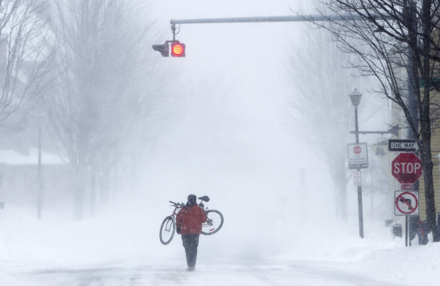 Juan Tavares carries his bike rather than risk riding on a snow-covered street during a blizzard, Saturday, Feb. 9, 2013, in Portland, Maine. The storm dumped more than 30 inches of snow as of Saturda