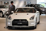A businessman look at car at the showroom of the Nissan headquarters in Yokohama, suburban Tokyo. Nissan on Friday posted a $4.28 billion full-year net profit and record sales as the Japanese automaker shrugged off the devastating impact of last year's quake-tsunami disaster on production