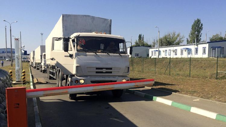 The first trucks from the Russian aid convoy wait to cross the border control point with Ukraine in the Russian town of Donetsk, Rostov-on-Don region, Russia, Saturday, Aug. 23, 2014. After traveling to besieged rebel-held areas, some of the trucks have now begun crossing back into Russia. (AP Photo/Alexander Roslyakov)
