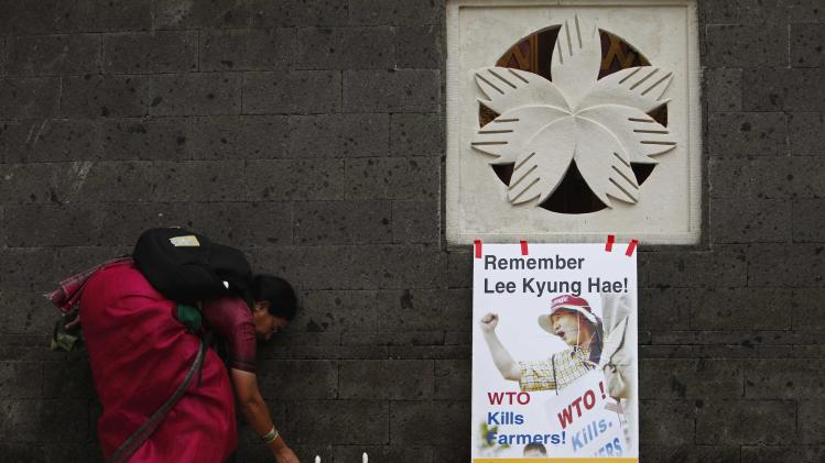 An activist picks up candles after offering candles and flowers, along with South Korean farmers, to honour the late Lee Hyung-hae at the ninth WTO Ministerial Conference in Nusa Dua