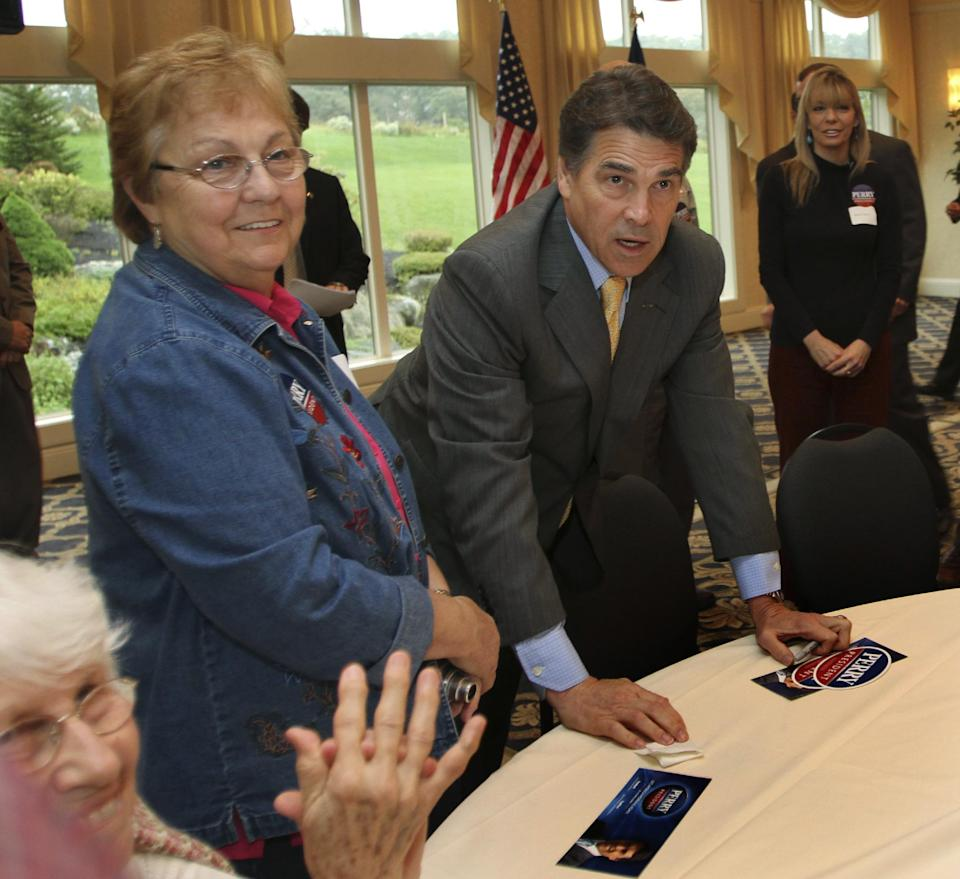 Republican presidential candidate, Texas Gov. Rick Perry, center right, greets supporters during a 2012 presidential campaign stop Saturday, Oct. 1, 2011 in Atkinson, N.H. (AP Photo/Jim Cole)