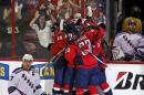 Teammates surround Washington Capitals left wing Andre Burakovsky, from Austria, after his game-winning goal as New York Rangers defenseman Ryan McDonagh (27) skates nearby, during the third period of Game 4 in the second round of the NHL Stanley Cup hockey playoffs, Wednesday, May 6, 2015, in Washington. The Capitals won 2-1. (AP Photo/Alex Brandon)