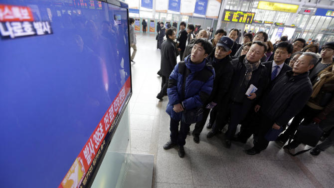 People watch a public TV reporting the country's first rocket launch at Seoul Railway Station in Seoul, South Korea, Wednesday, Jan. 30, 2013. South Korea says it has successfully launched a satellite into orbit from its own soil for the first time. Wednesday's high-stakes launch comes just weeks after archrival North Korea successfully launched its own satellite to the surprise of the world. (AP Photo/Lee Jin-man)