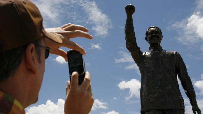 Unidentified man takes a photo of a giant statue of former South African President Nelson Mandela on Naval Hill, overlooking the city of Bloemfontein, South Africa, on Wednesday, Dec. 19, 2012.  The 94-year old anti-apartheid icon Nelson Mandela is spending a twelfth day in a South African hospital after being diagnosed with a lung infection and undergoing gallstone surgery.(AP Photo/Themba Hadebe)