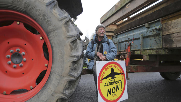 "FILE - This Nov. 17, 2012 file photo shows a demonstrator holding a sign reading: ""Airport No"", on a road near Notre Dame des Landes, western France, as part of a protest against a project to build an international airport, in Notre Dame des Landes, near Nantes. An unlikely alliance of anarchists and beret-wearing farmers is creating a headache for President Francois Hollande's beleaguered government by mounting an escalating Occupy Wall Street-style battle that has delayed construction on the ambitious airport near the city of Nantes for months. (AP Photo/David Vincent, File)"