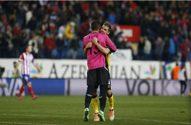 Sevilla's goalkeeper Beto hugs teammate Navarro at the end of their Spanish First Division soccer match against Atletico Madrid at Vicente Calderon stadium in Madrid