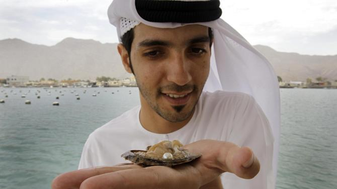In this Wednesday, April 4, 2012 photo, Mohamed al-Suwaidi from RAK Pearls Holding holds a cultured pearl inside an oyster shell after they have collected it from the sea farm in Ras al-Khaimah, United Arab Emirates. Long before the discovery of oil transformed the Gulf, the region's pearl divers were a mainstay of the economy. Their way of life, however, also was changed forever after Japanese researchers learned how to grow cultured pearls in 1930s. Now a collaboration between pearl traders in Japan and the United Arab Emirates had brought oyster farming to the UAE for the first time. (AP Photo/Kamran Jebreili)