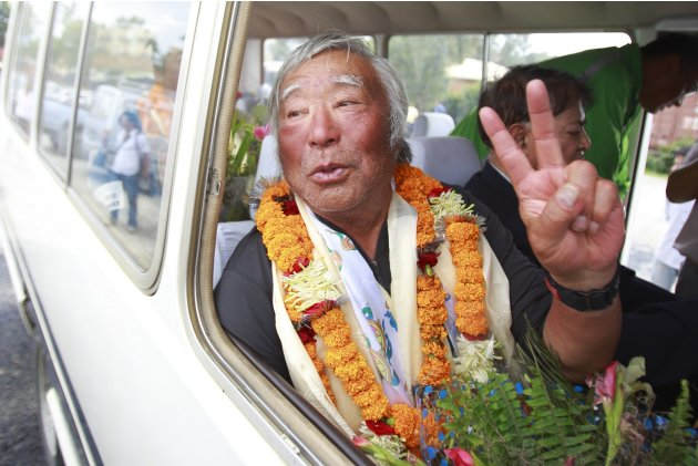 Japanese mountain climber Yuichiro Miura, 80, shows the victory sign upon his arrival at the airport after climbing Mount Everest, in Kathmandu