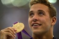 South Africa's Chad Le Clos poses on the podium after winning the gold medal in the men's 200m butterfly final of the London Olympics on Tuesday. Le Clos slept with his gold medal on after edging out US Olympics legend Michael Phelps in the 200m butterfly final, his South Africa team-mate Oscar Pistorius revealed Wednesday