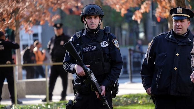 NYPD officers stand guard at the 9/11 memorial in New York on November 16, 2015, during a vigil for the victims of the Paris terrorist attacks